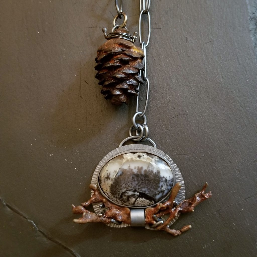 an image of the cast iron spruce cone and the dendritic agage pendant and cast iron lichen set at each end of the lariat