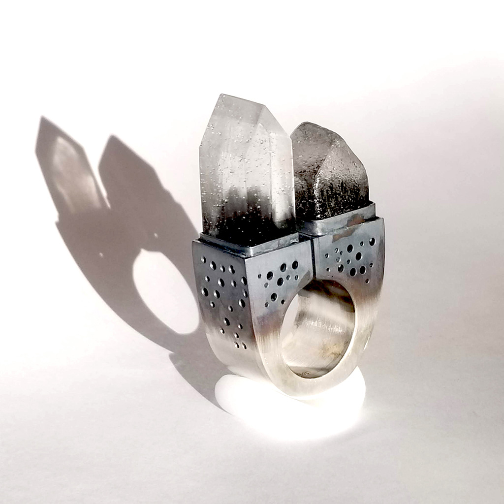 The American Dream: Fairbanks, AK is a hollow form statement ring made from silver. on the top are set two tiny glass houses